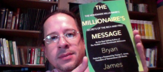 """Publisher Tony Michalski poses with Bryan James's new book """"The Millionaire's Message: The Homemade Millionaire's Secrets of the Rich and Free."""""""
