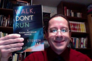 """Publisher Tony Michalski proudly displays Steven Jae Johnson's incredible and exciting book """"Walk, Don't Run: A Rockin' and Rollin' Memoir."""""""